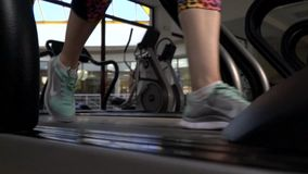 De vrouwelijke voeten in het runnen van tennisschoenen lopen op een tredmolen in de gymnastiek, langzame motie stock video