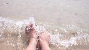 De vrouwelijke voeten op het zand, de overzeese golf behandelt de vrouwelijke benen 4k, langzame motie stock footage