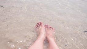 De vrouwelijke voeten op het zand, de overzeese golf behandelt de vrouwelijke benen 4k, langzame motie stock videobeelden