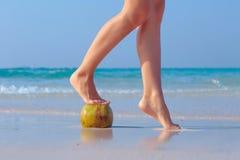 De vrouwelijke voeten propped op kokosnoot op overzeese achtergrond Stock Foto