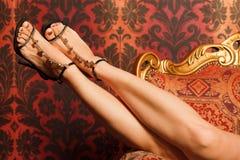 De vrouwelijke voeten in sandals zijn op rug van stoel Royalty-vrije Stock Afbeeldingen