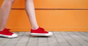 De vrouwelijke voeten in tennisschoenen die gumshoes langs oranje muur lopen, sluiten omhoog Vrouwen` s voeten in rode sportensch stock video