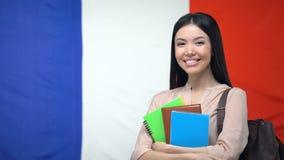 De vrouwelijke voorbeeldenboeken van de studentenholding tegen Franse vlag, internationaal onderwijs stock video