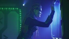 De vrouwelijke vreemdeling met dreadlocks en pantser gebruikt het groot scherm op de muur, 4k stock videobeelden