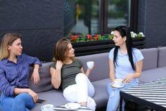 De vrouwelijke vrienden die van Nice en bij koffie, het drinken koffie lachen spreken Royalty-vrije Stock Foto's