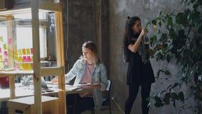 De vrouwelijke vrienden en de partners werken in modern bureau samen Het blonde zit bij lijst en het verzamelen stock video