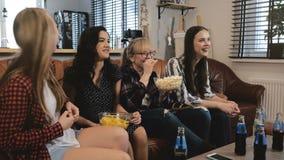 De vrouwelijke vrienden letten thuis komedie op film op TV De gelukkige meisjes lachen het letten op de grappige langzame motie v stock video