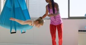 De vrouwelijke vrouw die van het traineronderwijs yoga doen die hangmat 4k met behulp van stock video