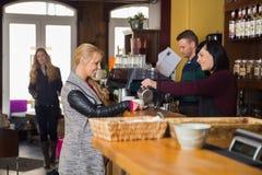 De vrouwelijke Vrouw van Barmanserving coffee to Stock Foto's