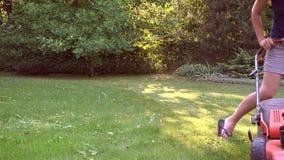 De vrouwelijke vrouwenbewegingen met grasmaaier en maait groen gras 4K stock videobeelden