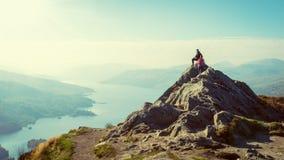 De vrouwelijke wandelaars bovenop de berg die van vallei geniet bekijken Stock Foto's