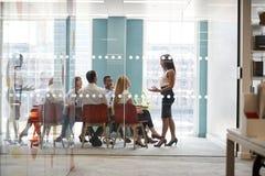 De vrouwelijke werkgever bevindt zich richtend collega's op commerciële vergadering royalty-vrije stock foto