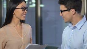 De vrouwelijke werkgever die mannelijke werknemers goedkeuren werkt, gelukkig met onderzoeksanalyse, zaken stock videobeelden