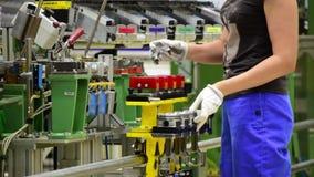 De vrouwelijke werknemer assembleert een motor van een auto stock videobeelden