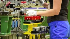De vrouwelijke werknemer assembleert een motor van een auto stock footage