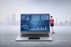 De vrouwelijke werknemer leunt op laptop met grafiek Stock Afbeelding