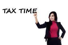 De vrouwelijke werknemer maakt een tekst van belastingstijd Royalty-vrije Stock Foto's