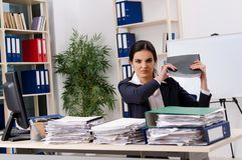 De vrouwelijke werknemer ongelukkig met het bovenmatige werk stock foto's
