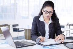 De vrouwelijke werknemer schrijft een dagboek in bureau stock fotografie