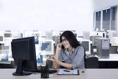 De vrouwelijke werknemer spreekt de groeigrafieken telefonisch Stock Afbeeldingen