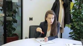 De vrouwelijke werknemer spreekt het gesticuleren terwijl het zitten in modern bureau stock video