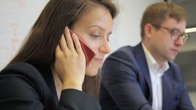 De vrouwelijke werknemer spreekt op telefoon, zittend naast collega in bureau stock footage