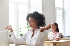 De vrouwelijke werknemers die in mudra mediteren plaatsen in bureau royalty-vrije stock afbeelding