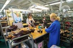 De vrouwelijke werknemers maken schoenen bij een schoenfabriek Stock Afbeeldingen