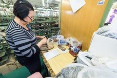 De vrouwelijke werknemers maken schoenen bij een schoenfabriek Stock Fotografie