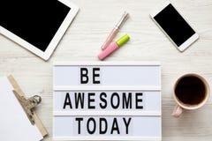 De vrouwelijke werkplaats met tablet, noticepad, blad, koffie en ` is ontzagwekkende vandaag `-woorden op licht vakje over wit ho royalty-vrije stock foto