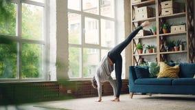De vrouwelijke yogainstructeur oefent alleen thuis doen uit complex van asanas zich bevindt op vloer en bewegend lichaam Gezond stock videobeelden