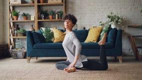 De vrouwelijke yogaleraar toont aan de Koning Pigeon stelt, sprekend aan sociale media abonnees en het glimlachen het bekijken ca stock video
