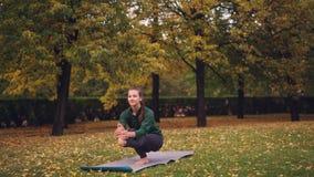De vrouwelijke yogastudent brengt op één been in evenwicht die zich op mat die op recreatief gebied bevinden alleen op de herfstd stock video