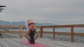 De vrouwelijke yogatrainer toont posities, die buitenkant bevinden zich dichtbij zeekust stock footage