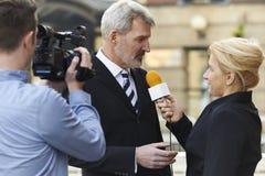 De vrouwelijke Zakenman van Journalistwith microphone interviewing Stock Afbeelding