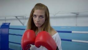 De vrouwelijke zelf-defensie, jonge vrouwenbokser werkt slagen bij camera op ring uit stock footage
