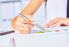 De vrouwelijke zilveren pen van het handpunt aan bedrijfsgrafiek op seminarie Het bankkrediet, leningsgeld, investeert, het overz royalty-vrije stock afbeeldingen