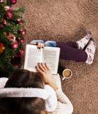 De vrouwelijke zitting op vloertapijt en de lezing boeken naast Kerstboom en koffiekop stock afbeeldingen