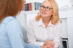De vrouwelijke zitting van de psychologysttherapie met cliënt die binnen het spreken zitten aan geduldig close-up royalty-vrije stock afbeelding