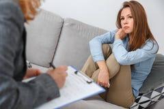 De vrouwelijke zitting van de psychologysttherapie met cliënt die binnen meisje zitten die nadenkend therapeut bekijken stock foto's