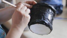 De vrouwelijke zwarte geschilderde hand van de kunstenaarsvernis - gemaakte emmer met een borstel en een lak stock video