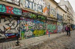 De vrouwen bekijken de kleurrijke graffiti op Rue Denoyez in Parijs Stock Foto