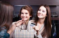 De vrouwen betalen met creditcard en halen koopjes weg Stock Foto