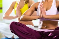 De vrouwen in de gymnastiek die yoga doen oefenen voor geschiktheid uit Royalty-vrije Stock Foto