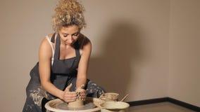 De vrouwen die aan de pottenbakker ` s werken rijden De handen beeldhouwt een kop van kleipot stock footage