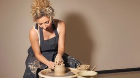 De vrouwen die aan de pottenbakker ` s werken rijden De handen beeldhouwt een kop van kleipot stock afbeeldingen