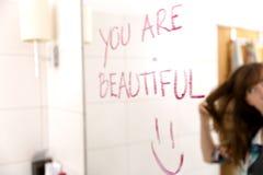 De vrouwen die aanmoedigen door woorden te schrijven u zijn mooi op spiegel met lippenstift stock foto
