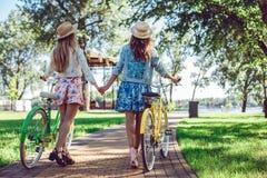 De vrouwen die in de zomer lopen parkeren holdingshanden kijkend in de zonsondergang met hun fietsen stock afbeeldingen