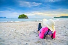 De vrouwen die hoeden dragen slapen op het strandoverzees stock foto's