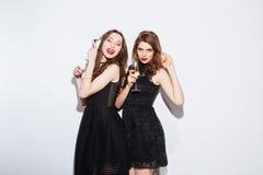 De vrouwen die in nacht stellen kleden zich met glas champagne Royalty-vrije Stock Foto's